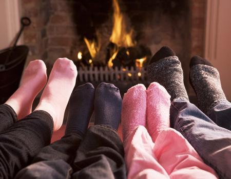 Immagine della tipica 'ricchissima' famiglia italiana che si riscalda i piedi davanti il caminetto acceso.