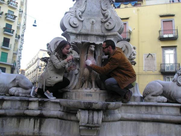 Luca De Martino e una ragazza puliscono una delle aquile della fontana Carlo III